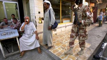Religiøse spændinger og USA's tilstedeværelse er langt fra hele forklaringen på Iraks problemer. Mænd drikker te i Bagdad, mens en irakisk soldat på patrulje med amerikanske soldater går forbi.