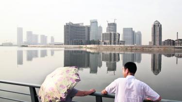 Et par står og kigger på det nye finansdistrikt – også kaldet Østens Manhattan – i byen Tianjin.