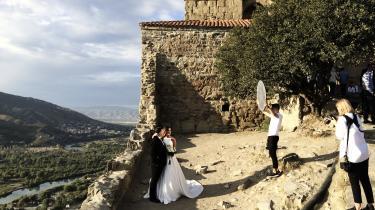 Brudeparret poserer for fotograferne foran et gammelt kloster. Gommens far allerede har overrakt sin bryllupsgave: En penthouselejlighed midt i Tbilisi.