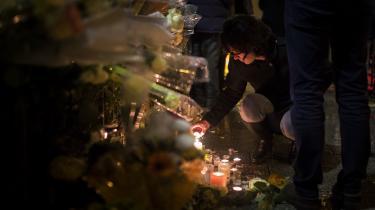 En kvinde tænder et lys foran spillestedet Bataclan i Paris på årsdagen for terrorangrebet i byen.
