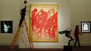 Et værk af Cy Twomble bliver tilpasset af en medarbejder på Sotheby's.