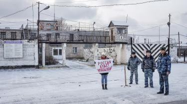 En kvinde holder et skilt, hvor der står »Rusland bliver frit« til støtte for oppositionsaktivisten Ildar Dadin, som sidder fanget i fængslet bag hende, fordi han ene mand gik op mod Kreml og protesterede mod krigen med Ukraine. Iølge Dadin har fængselsvagter torteret ham og truet med at voldtage og dræbe ham.