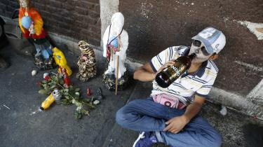 Den katolske kirke ser med skeptiske øjne på mexicanernes tiltagende dyrkelse af dødsgudinden Santa Muerte, som Thomas Boberg opsøger i 'Mexicocitydigte'. Han søger ind i Mexico Citys berygtede sortbørsområde Tepito, hvor turister frarådes at komme. På billedet ses 18-årige Brandon Josue Fuentes netop i Tepito, hvor han drikker til ære for Santa Muerte, som der er et særligt tempel for i Tepito.
