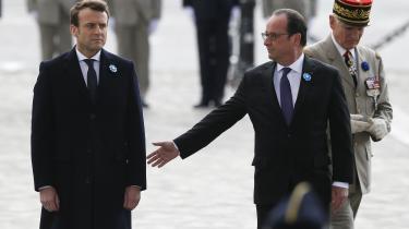 Den nuværende præsident François Hollande rækker ud efter den kommende præsident Emmanuel Marcon under en ceremoni tirsdag for afslutningen af Anden Verdenskrig. Marcon vandt det franske præsidentvalg ved at lægge afstand til den kendte form for politik med partier og fløje