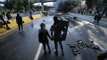 24. april, 2017: Foran en vejblokade i hovedstaden Caracas holder et par hinanden i hånden under demonstrationerne mod Venezuelas styre.