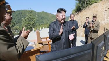 Et billede udsendt af nordkoreanske myndigheder, der angiveligt viser Kim Jong-unfejre affyringen af etinterkontinentalt balistisk masil.