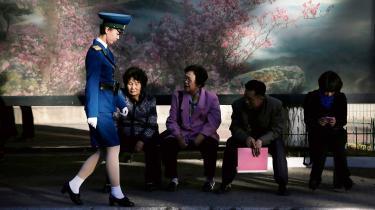 En nordkoreansk trafikbetjent går forbi borgere i Pyongyang, der venter på bussen efter en lang arbejdsdag i 2016. I takt med at Nordkoreas præsident, Kim Jong-un, har åbnet op for landets tøjindustri, er kvindernes kjoler langsomt sneget sig op over knælængde.