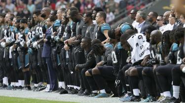 Den jakkesætklædte mand med det store overskæg, Shahid Khan, er ejer af NFL-holdet Jacksonville Jaguars og erklæret republikaner. I søndags protesterede han mod Donald Trump sammen med sine spillere.