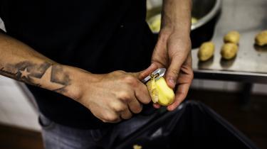 En ung mand aftjener sin samfundstjeneste påDemenscentret Bryggergården ved blandt andet at skrælle kartofler i køkkenet