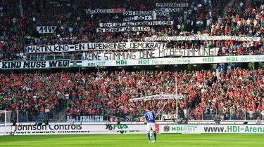 Ved Bundesligaens premierekamp mod Schalke 04 opfordrede et banner Hannover 96's klubpræsident, Martin Kind, til at gå af. 'Kind muss weg,' stod der.