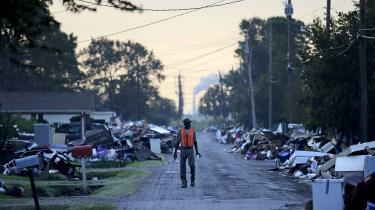 En arbejder går forbi skraldet, der langsomt er ved at blive ryddet op efter Harvey blandt andet byen Port Arthur i Texas.