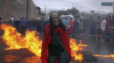 Efter lang tid med uroligheder er den siddende præsident blevet kåret som vinder af valget i Honduras. Her er det en maskeret demonstrant foran en brændende barrikade i Tegucigalpa, Honduras den 18. december.
