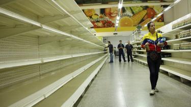 En kvinde går forbi de tomme supermarkedshylder i San Cristobal i Venezuela. Plyndring på grund af sult forekommer nu hyppigt i landet.