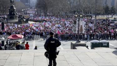 En betjent ser ud over de forsamlede til søndagens protest i Philadelphia. Demonstrationen er en opfølgning på kvindemarchen efter indsættelsen af Trump sidste år.