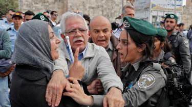 En mand forsøger at skille en palæstinensisk kvinde og en israelsk grænsevagt, der er kommet i klammeri d. 13. maj, hvor israelske nationalister fejrede Jerusalem Day.