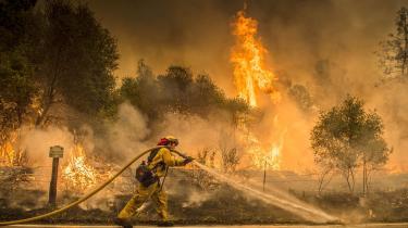 En brandmand på arbejde nær byen Igo i Californien. De mange naturbrande har været svære at få bugt med på grund af uberegnelige vindstød.