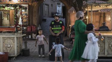 Børn leger omkring en lokal politibetjent i den gamle bydel i Kashgar, der ligger i den fjerneste vestlige del af Xinjiang-provinsen tæt ved Kirgisistan. Den lokale muslimske uighurerbefolkning bliver truet og opdraget til at opgive dets kulturelle rødder.