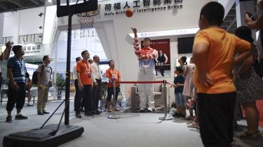 Besøgende kigger på en industrirobot på en robotkonference i Beijing. USA forsøger med nye toldafgifter at ramme den kinesiske regerings nationale industriplan kaldet Made in China 2025. Den går ud på at fremtidssikre Kina ved at opgradere ti udvalgte industrier som for eksempel robotteknologi, kunstig intelligens og højhastighedstog.