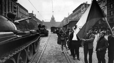 Pragborgere på gaden i august 1968. De bærer et blodplettet tjekkoslovakisk flag i protest mod indrullende tanks.