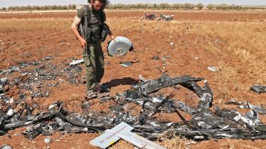 En oprørskriger inspicerer, hvad der formodes at være resterne af en drone fra det syriske regime. Under den syriske borgerkrig har også Islamisk Stat brugt droner.