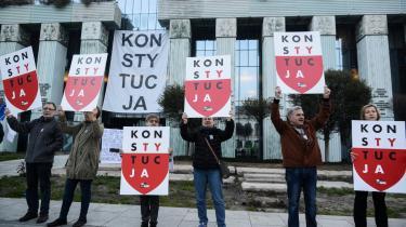 I Polen har regeringen reformeret retsvæsnet ved bl.a. at tvangspensionere en række højesteretsdommere, hvilket ifølge en afgørelse fra EU-Domstolen er ulovligt. På billedet ses demonstranter, der skilter med ordet 'konstitution' foran højesteretten i Warszawa.