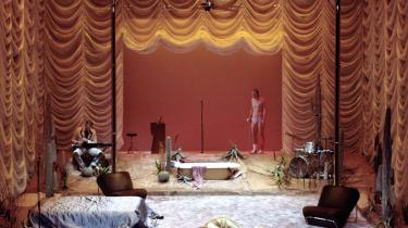 Scenograf Christian har glam'et soveværelsesscenen op i sand Dallas-stil med høje kunstige guldpalmer, henkastede pailletkjoler og dekadent skinnende draperier. Det iscenesætter smukt de gyldne facader af løgne og ikke mindst den familiære invasion af det intime rum, der både er den store komiske og kritiske kraft i Kat på et varmt bliktag.