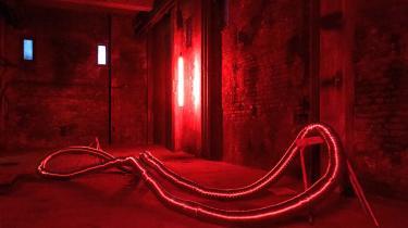 I det røde lys snor skulpturen Atrofi (græsk for en mager krop) sig, en lang grå slange i aluminium, holdt oppe af gammeldags bordbukke.