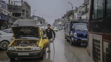 En taxachauffør, som har mistet benet, står ved siden af sin bil i byen Raqa i det nordlige Syrien. Den syriske borgerkrig har i næste måned varet i otte år, og den russiske præsident Putin har ikke travlt med at standse konflikten.