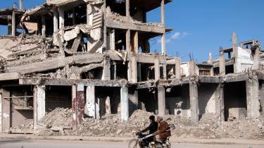 To syriske mænd kører forbi destruerede bygninger i densidste lomme af land, som den militante gruppe IS har haft kontrol over i Syrien.
