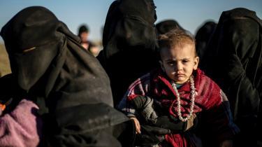 En gruppe kvinder venter på at blive ransaget af kurdiske soldater efter at have forladt IS' sidste tilholdssted i Baghouz i det østlige Syrien.