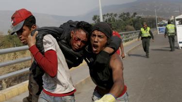 Demonstranter bærer den 25. februar i år en tilskadekommet væk under et sammenstød med Venezuelas sikkerhedsstyrker på Simon Bolivar-broen, der går på grænsen mellem Venezuela og Cúcuta i Colombia. Mange demonstranter er strandet i Cúcuta, da det venezuelanske styre har sat en pris på deres hoveder, og de derfor ikke tør vende hjem.