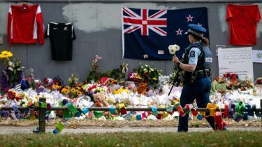 En politibetjentpå vej til at lægge blomster til ære for ofrene ved terrorangrebet i Christchurch.