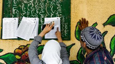To egyptiske vælgere kigger her på en listeover stemmesteder til folkeafstemningen om en ny forfatningen. Mange især i den ældre generation har stemt ja til forfatningen i håb om at bevare stabiliteten i Egypten, selvom oppositionen i begyndelsen af april formulerede et fælles nej.