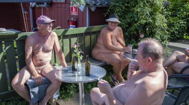 Rene Ringsholm (kasket), Thorkild Jørgensen og Marianne hygger med en øl i varmen på Naturistcamping Solbakken.