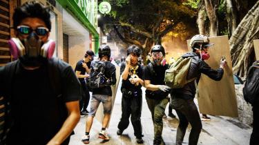 Unge aktivister i Hongkong beskytter sig mod politiets tåregasangreb. »Free Hong Kong!« råber demonstranterne i takt under en demonstration i shoppingdistriktet Tsim Sha Tsui. Her ligger luksusbutikker som Armani, Gucci og Bulgari side om side. Butikspersonalet er hurtige til et dreje nøglen om, så snart de ser optoget.