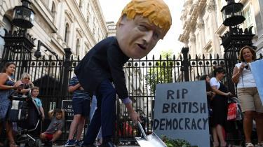 »Selv om Boris Johnsons suspendering af parlamentet ikke er ulovlig, og til en vis grad kan forklares, så er den alligevel demokratisk skandaløs,« skriver lederskribenten Christian Bennike. Her ses en demonstrant-som er iførten maske, der skal forestille Boris Johnson - demonstrere imodsuspenderingen af parlamentet.