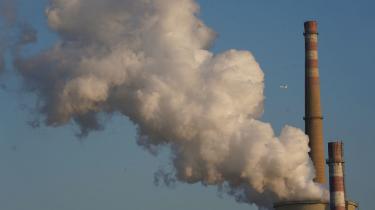 Røgen stiger op fra et kraftværk ved Beijing, Kinas hovedstad. Og i baggrunden passerer et fly, mens også det udleder drivhusgasser.