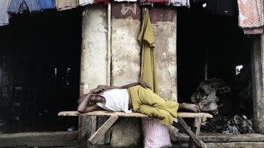 I slumkvarteret Susans Bay, Freetown, har en mand fundet en bænk og et sted til en lur midt i kaos omkring ham.