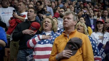 Da nationalsangen bliver sunget, tager alle deres kasketter af og vender sig mod flaget, som hænger bag den stol, hvorfra Trump skal tale.