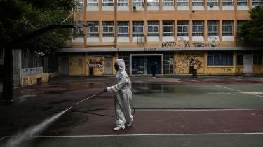 En arbejder desinficerer en skolegård i Athen forud for genåbningen af skolerne for de ældre studerende. Grækenland indførte en hurtig og omfattende nedlukning for at afværge et truende pres på et udsultet sundhedssystem.