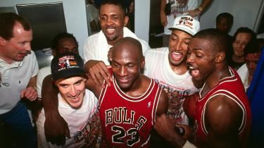 Michael Jordan omgivet af sine glade holdkammerater i Chicago Bulls, da de lige har vundet endnu et NBA-mesterskab i dokumentarfilmserien 'The Last Dance'. Det er Scottie Pippen med kasket til højre for Jordan, og John Paxson til venstre, også med kasket.