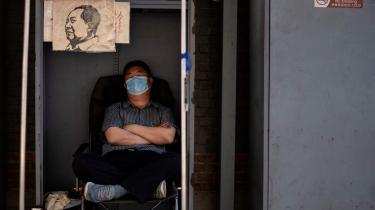 En boghandler tager en lur, mens han venter på kunder i sin butik på et marked i Panjiayan i Beijing.
