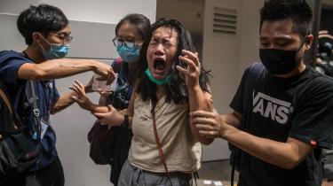 Allerede kort efter en ny lov trådte i kraft i Hongkong blev aktivister anholdt. På billedet har en kvinde fået politiets peberspray i øjnene.