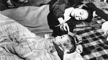 I en bank omdannet til nødhospital to måneder efter atombomben i Hiroshima i 1945 tilser en japansk kvinde sit barns skader.