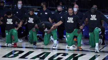 I The Bubble bor, træner og spiller NBA-stjernerne i sikker isolation fra det coronaramte USA, men spillerne har insisteret på en aktivistisk forbindelse til vreden uden for boblen. BLACK LIVES MATTER står der på spillernes overtrækstrøjer, og under nationalsangen inden kampene knæler næsten alle spillerne i solidaritet med kampen mod racisme. Her er det spillere fra Boston Celtics forud for kampen mod Washington Wizards.