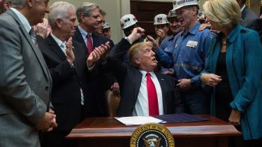 Præsident Donald Trump giver en kuglepen til nogle kulminearbejdere. Pennen har han brugt til at underskrive et lovforslag, der afskaffer reguleringer af mineindustrien.