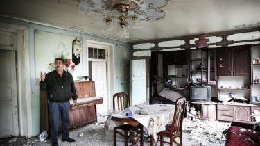 En mand står i en lejlighed, der er blevet ødelagt efter et påstået armensk angreb på byen Tartar.