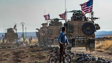 En syrisk dreng følger en amerikansk militærkolonne i Syrien tæt på den tyrikiske grænse. Selv om Trump har forsøgt at trække USA ud af verdenen, er der i dag flere amerikanske tropper på jorden i Mellemøsten, end da han tog over.