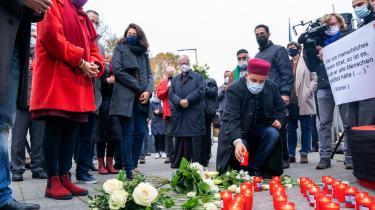 En mand stiller et lys på fortorvet for at mindes ofrene for terroren i Wien.