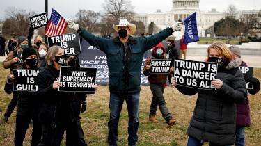 Anti-Trump demonstration uden foran Kongressen, som dagen forinden blev stormet af oprørere. I midten ses en Trump tilhænger, som viser flag fra Trumps præsidentkampagne.